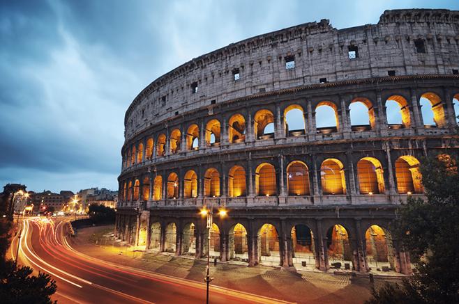 Das Kolosseum in Rom ist ein beliebtes Fotomotiv, da es abends beleuchtet ist. Die hellen Schlieren links im Bild sind übrigens voreifahrende Autos, deren Lichter durch die Langzeitbelichtung verwischen.
