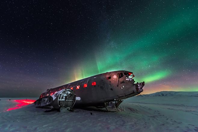 Wer richtig Glück hat und zur richtigen Jahreszeit in die nordischen Länder reist, kann die Polarlichter sehen. Hier explodieren sie gerade hinter einem Flugzeugwrack in Island.