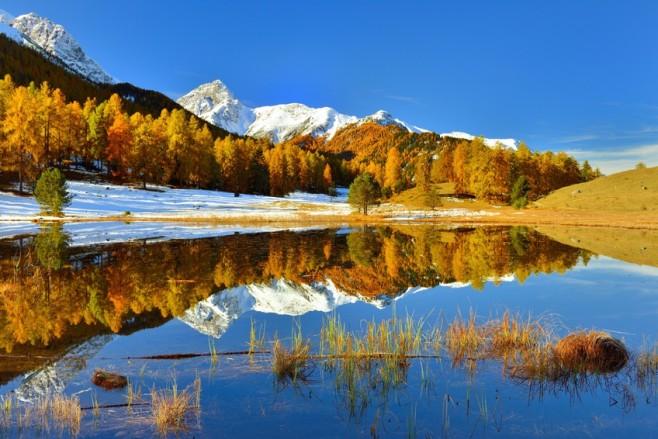 Spiegelung einer herbstlichen Landschaft in einem ruhigen Bergsee in der Schweiz